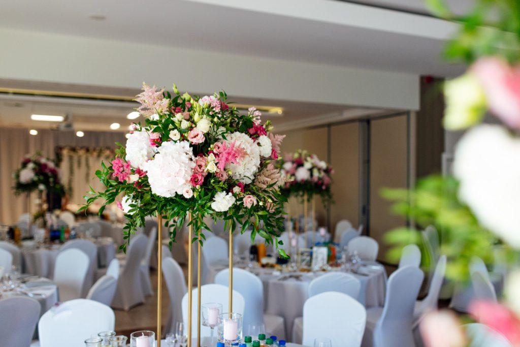kompozycja z różowych hortensji, eustomy i tawułek z dodatkiem zieleni na złotym geometrycznym stojaku