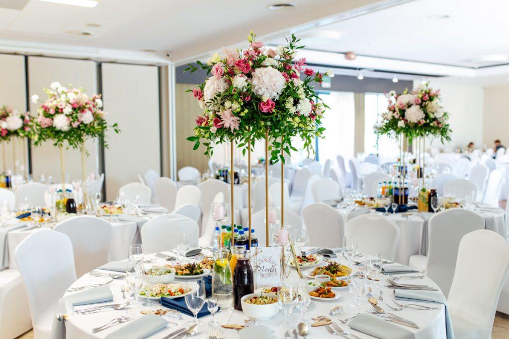 kwiatowe kompozycje z dużą ilością zieleni na wysokich geometrycznych stojakach jako dekoracja stołów gości na wesele