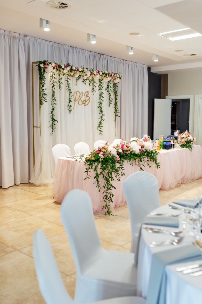 dekoracja stołu pary młodej i ścianki tiulowymi materiałami oraz zwisającą zielenią