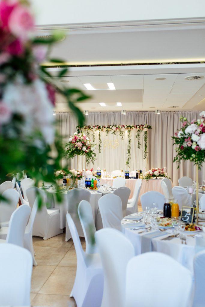 dekoracja miejsca wesela w ogrodowym stylu z różowych kwiatów i zieleni