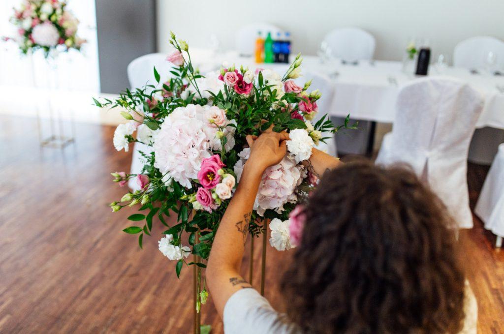 florystka uzupełniająca wysoką kompozycję kwiatową na złotym stojaku