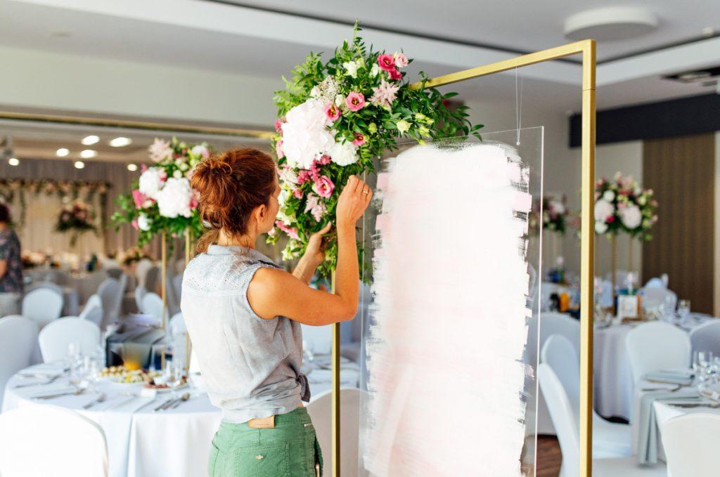 florystka poprawiająca kwiaty dekorujące tablicę z planem stołów