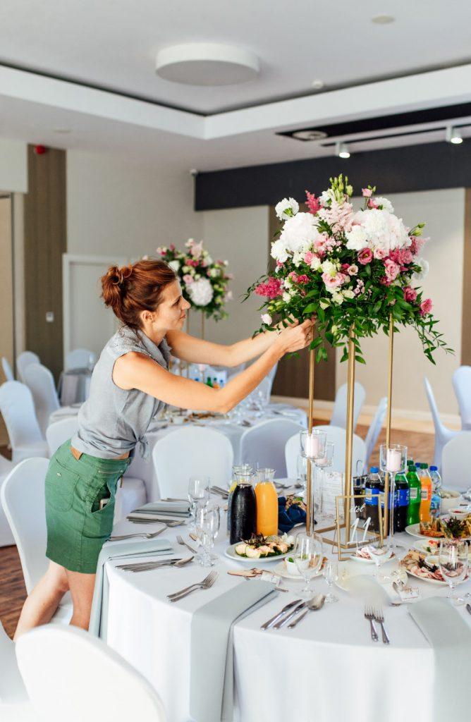 florystka poprawiająca kompozycje kwiatową dekorującą stół gości na sali weselnej
