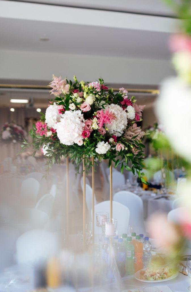 kompozycja kwiatowa w różowych odcieniach z zielenią na złotym geometrycznym stojaku jako aranżacja stołu