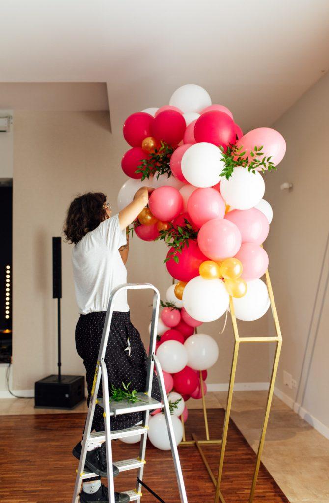 dekoratorka uzupełniająca kompozycję z balonów jako tło do zdjęć