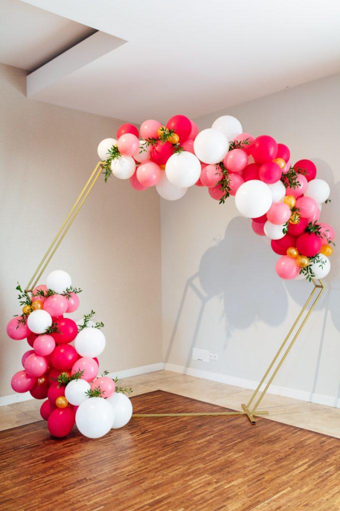 dekoracja balonowa z białych i różowych balonów oraz z zielonymi listkami na złotym heksagonie