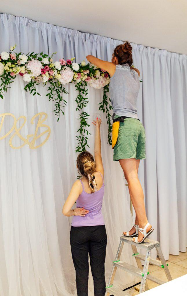 florystki dekorujące ściankę za państwem młodych