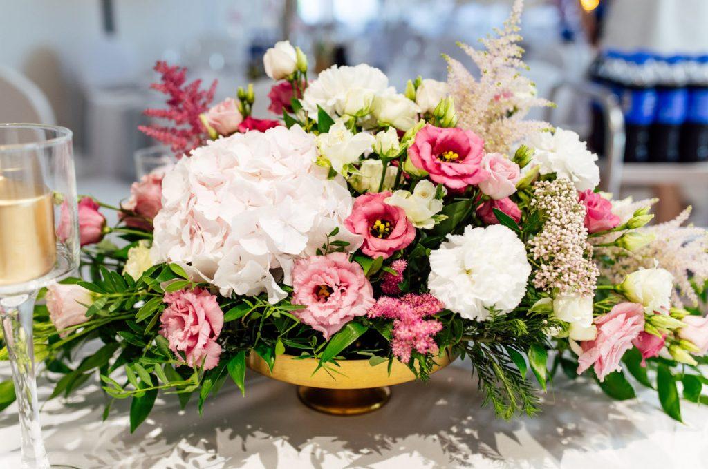 kompozycja kwiatowa z zielenią w złotej wazie w ogrodowym stylu jako dekoracja stołu