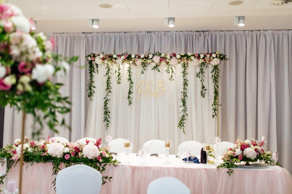 dekoracja stołu i tła za Parą młodą w kolorze biało różowym z dodatkiem zieleni